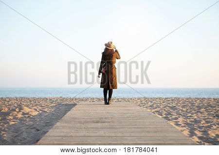 Portrait Of White-skinned Lady Standing Back To Camera On Boardwalk Looking At Blue Sea Wearing Clas