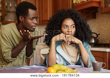 Candid Shot Of Unhappy Young Afro-american Couple Having Quarrel At Home: Guilty Regretful Man Weari