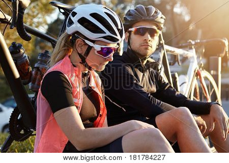 Close Up Outdoor Portrait Of Two Friends, Male And Female, In Sportswear, Sitting On Grass In City P