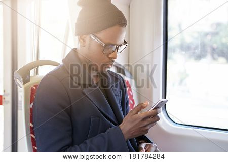 Serious Young Black Male In Trendy Rectangular Glasses Looking Through Pcitures Via Social Media, Us