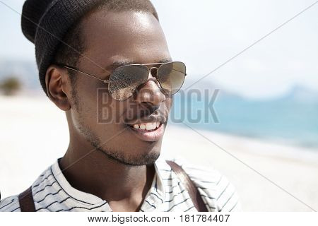 Close Up Shot Of Happy Young African American Backpacker In Mirrored Lens Sunglasses Relaxing On Bea