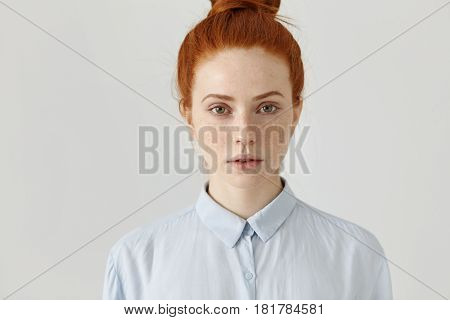 Close Up Shot Of Attractive Successful Young Red-haired Businesswoman In Formal Shirt Having Serious