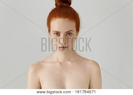 Head And Shoulders Of Attractive Young Female Model With Ginger Hair Bun And Freckles Posing Topless