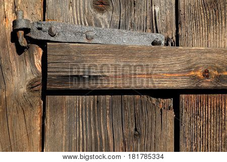 old hand-forged hinges on old wooden door