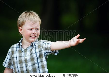photo of young crying boy in summer park