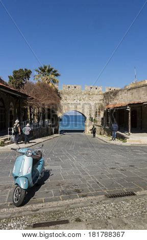 17TH FEBRUARY 2017, RHODES, GREECE - View of the sea through one of the city gates in the old town of Rhodes Greece with a motor scooter in the foreground
