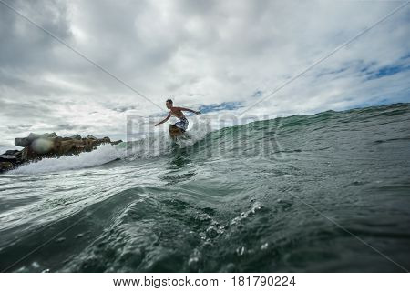Pensive man in swimming with surfboard