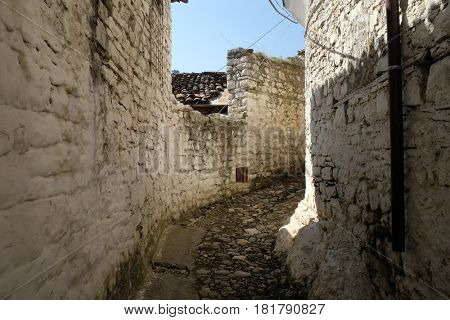 BERAT, ALBANIA - OCTOBER 01, 2016: Narrow cobble stone street with traditional ottoman white stone houses in Old town Berat, Albania on October 01, 2016.