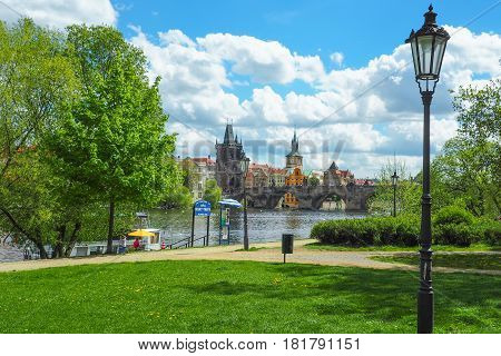 View of the Prague skyline and Charles Bridge from Vltava riverside on a sunny spring day.
