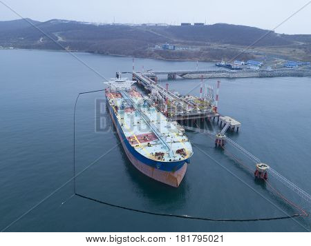Liquid bulk oil tanker in port Fenced with booms