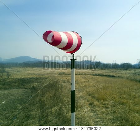 Red-white windsock indicating wind with blue sky