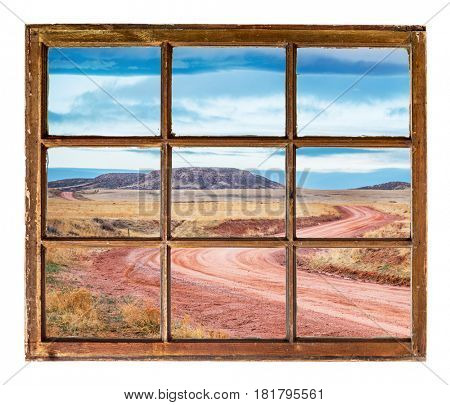 windy ranch road in Colorado foothills as seen  through vintage, grunge, sash window with dirty glass