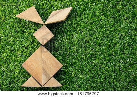 Wooden tangram puzzle in rabbit shape on artificial green grass background (Concept of Happy Easter)