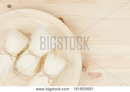 Sheafs raw asian cellophane noodles on plate on beige wooden board with copy space top view.