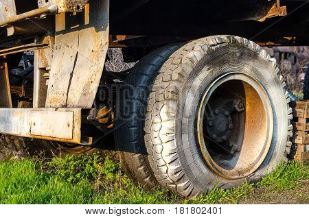 Flat tire of an old fragment of a rusty abandoned broken truck