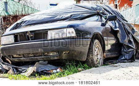 Old broken car after the accident covered with tarpaulin