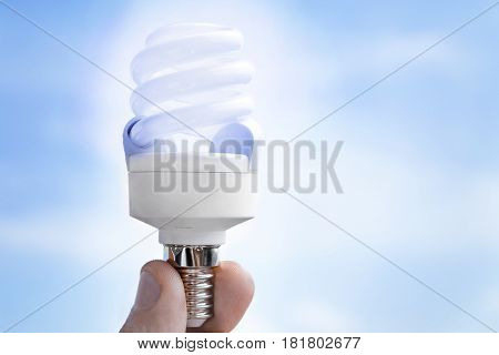 energy saving lamp in hand on blue sky background