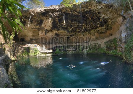 VALLADOLID YUCATAN MEXICO - FEBRUARY 23 2017: The cool blue waters of this natural underground pool called Cenote Zaci provides tourists relief from the hot dry climate common in this part of Mexico.