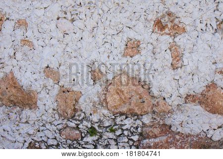 Very rustic and rough textured exterior wall made of stone and white stucco in colonial Mexican city