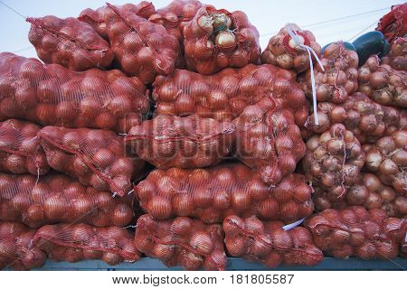 Onions in red plastic mesh sacks and bags in grid on a car