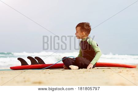 Surfer boy watching the waves, portrait of little boy learn to surf at sea