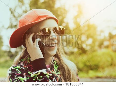 Teenager girl smiling and laughing loudly talking on the mobile phone.
