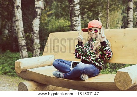 Beautiful girl sits on wooden bench in a Park and listens to music.