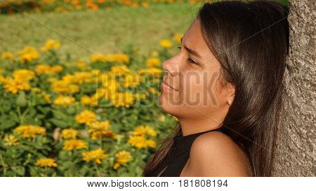 Girl Relaxing In Park Leaning Against a Tree