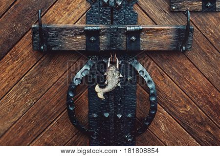 old medieval castle door with forged lock in the form of fish.