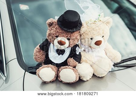 small plush bears on a wedding. Decoration on the car hood.