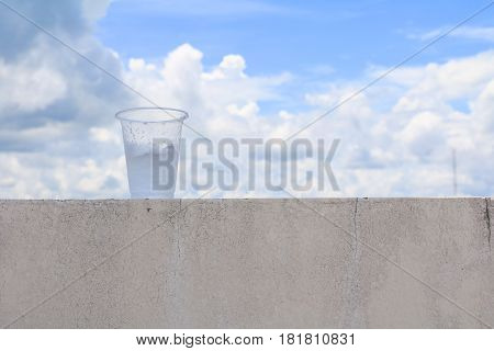 ice in glass-plastic on the floor with blue sky background