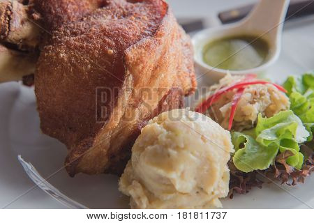 Pork knuckle with fried and mash potato on a white plate .