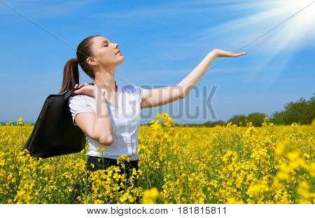 Business woman with briefcase show palm to sun. Young girl in yellow flower field. Beautiful spring landscape, bright sunny day, rapeseed