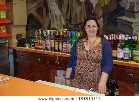 SANTA SUSANNA, CATALONIA, SPAIN - JUNE 13: Smiling woman is standing at counter in bar on many bottles background on June 13, 2014 in Santa Susanna, Catalonia, Spain.