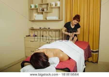 attractive massage therapist, woman doing relaxing feet massage , in a spa center. Wellness legs massage