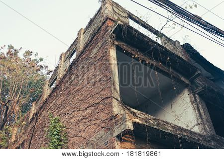View Of Exterior Of An Old Abandoned Unfinished Brick Wall House With Overgrown Gapes Of Brown And V