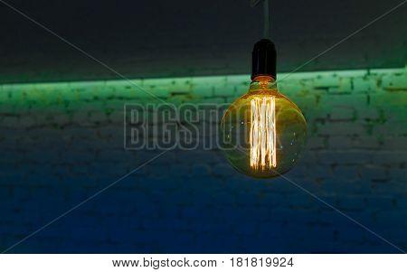 decorative lighting spiral bulb against a brick wall