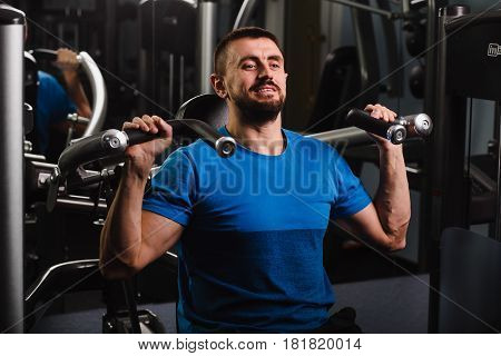 muscular, attractive man trains his arm muscles, doing exercises to build muscle in his arms and back. Workout at gym