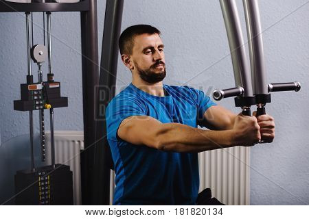 muscular, attractive man trains his torso muscles , doing exercises on a butterfly machine with weights, at gym.