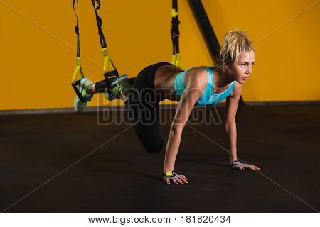 Sporty woman doing pushups using suspension straps, at gym. Suspension training for slim body. Exercises for beautiful hand