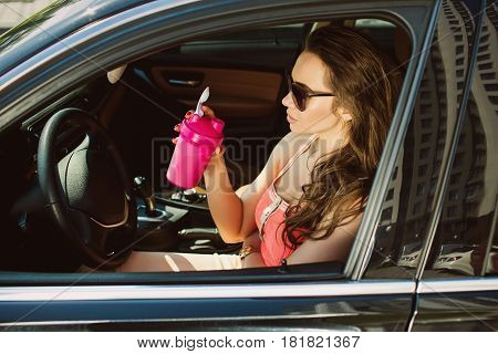 successful woman, dressed in casual clothes, drinks sports food, sitting in a luxurious car. Healthy eating everywhere