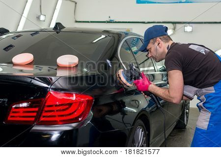 A man polishes a black car with a polishing machine