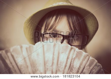Fashionable little girl looks slyly from under the fan.