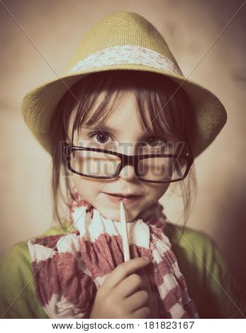 Fashionable little girl with a pencil in hand thinking.