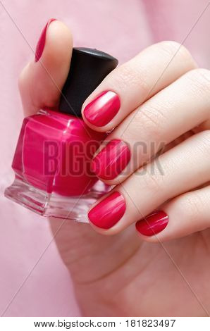 Beautiful female hand with pink nail design holding nail lacquer bottle.