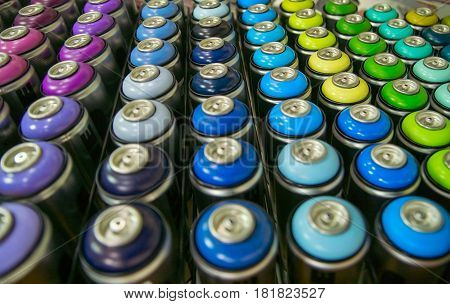 colorful cans of paint stand rows on a shelf