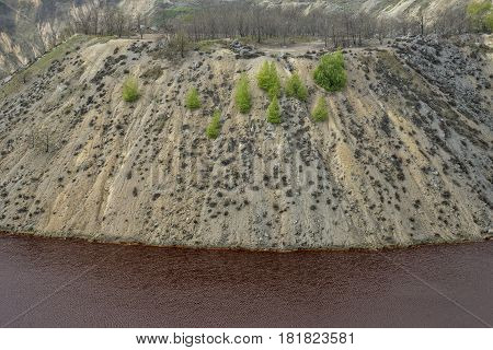 Red artificial lake and hills as a result of mining and production of copper