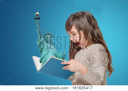 Surprised long haired little girl holding open book in her hands. From the book is protruding Lady Liberty. All is on the blue gradient background.