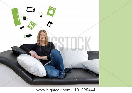 Grinning long haired young woman is sitting on a black and white couch with black and white pillows. Woman is looking upwards on the illustration of a home appliance in the background. Empty green color rectangle is ready for your text.