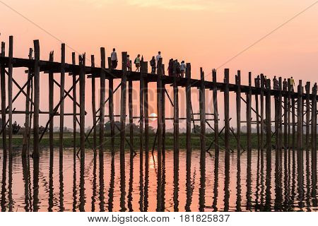 U Bein Bridge at sunset with people crossing Ayeyarwady River at Mandalay Myanmar